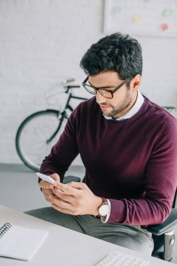 handsome designer in burgundy sweater using smartphone in office