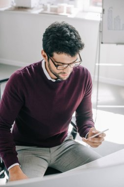 handsome businessman in burgundy sweater using smartphone in office