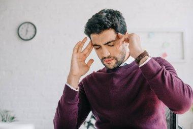 tired businessman in burgundy sweater having headache in office