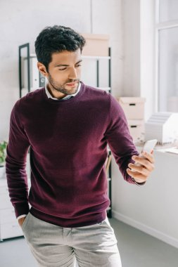 handsome designer in burgundy sweater looking at smartphone in office