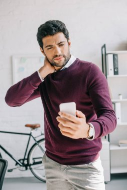 handsome businessman in burgundy sweater looking at smartphone in office
