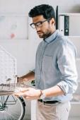 boční pohled pohledný architekt drží model architektury v úřadu