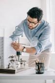 Fotografie pohledný architekt pracuje s model architektury na stole v kanceláři