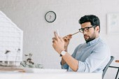 shocked architect using smartphone near architecture model in office