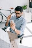 vážnou architekt pomocí smartphone poblíž model architektury v kanceláři