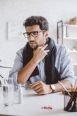 sick manager in scarf touching painful throat in office