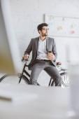 pohledný podnikatel sedí na kole a držení kávu v kanceláři