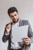 vážný podnikatel čtení dokumentů a dotyku hlavy s tužkou v úřadu