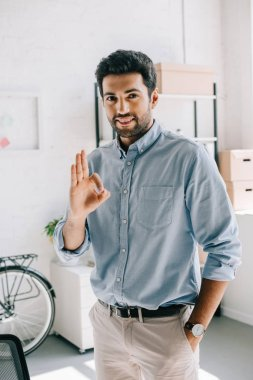 handsome cheerful architect showing okay gesture in office