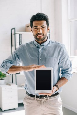 handsome smiling architect showing tablet with blank screen in office