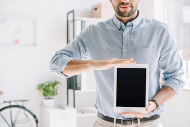 cropped image of architect showing tablet with blank screen in office