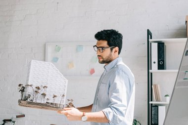 side view of handsome architect in glasses holding architecture model in office