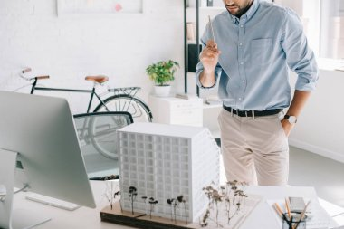 cropped image of architect holding pencil and standing near architecture model on table in office