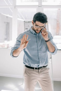 handsome architect talking by smartphone and gesturing in office