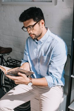 handsome architect with bristle reading book in office