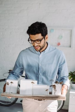 handsome smiling architect holding architecture model in office