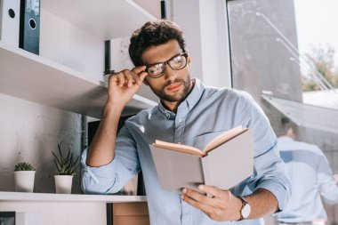handsome architect touching glasses and reading book in office