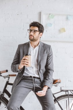 businessman listening music with smartphone, holding cup of coffee and leaning on bike in office
