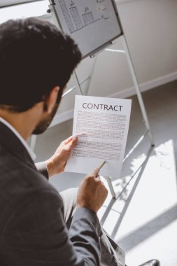 high angle view of businessman reading contract in office