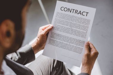 cropped image of businessman reading working contract in office