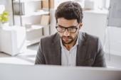 pohledný podnikatel v brýlích na počítač v kanceláři