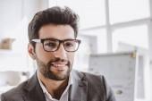 portrét usměvavý pohledný podnikatel v brýlích při pohledu na fotoaparát v úřadu