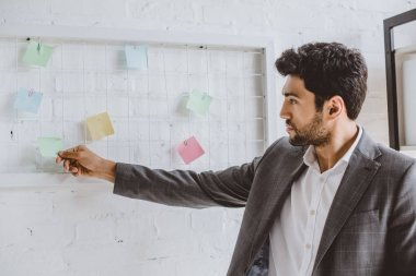 handsome businessman taking sticker from task board in office