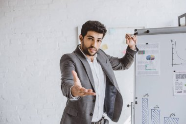handsome businessman gesturing while presenting project on flipchart in office