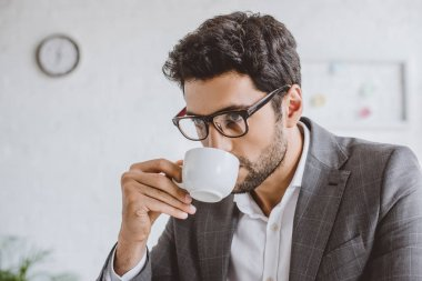 portrait of handsome businessman drinking coffee in office