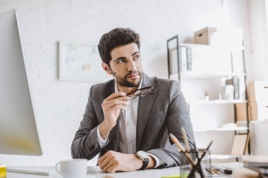 handsome businessman holding glasses and looking away in office