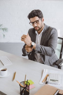 handsome businessman wearing wristwatch in office