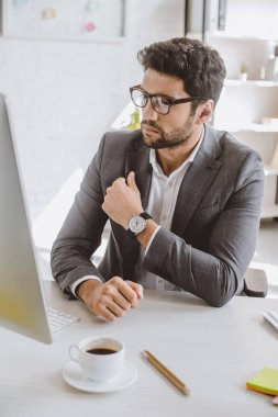 handsome businessman in glasses looking at computer in office