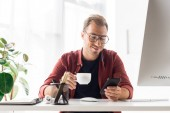 Fotografie businessman with cup of coffee using smartphone in modern office
