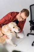 Fotografie man hugging golden retriever dog near chair