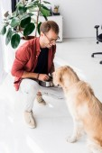 Mann in Gläsern Fütterung golden Retriever Hund