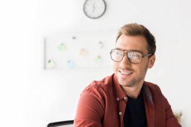 smiling businessman in glasses looking away