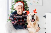 Photo man in christmas sweater and santa hat stroking golden retriever in deer horns