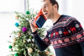 Fotografie man in christmas sweater with gift box near head against christmas tree