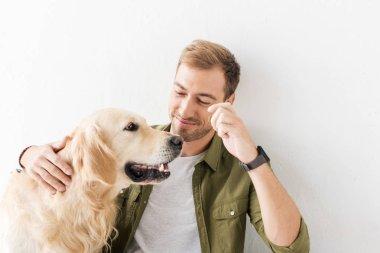 man stroking golden retriever dog against white wall