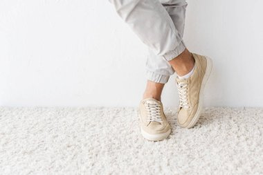 cropped view of casual man standing on beige rug