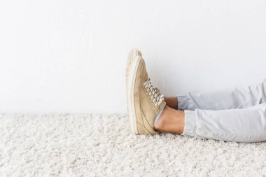 cropped view of casual man on beige rug
