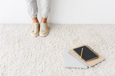 cropped view of casual man standing on beige rug with laptop and notebooks