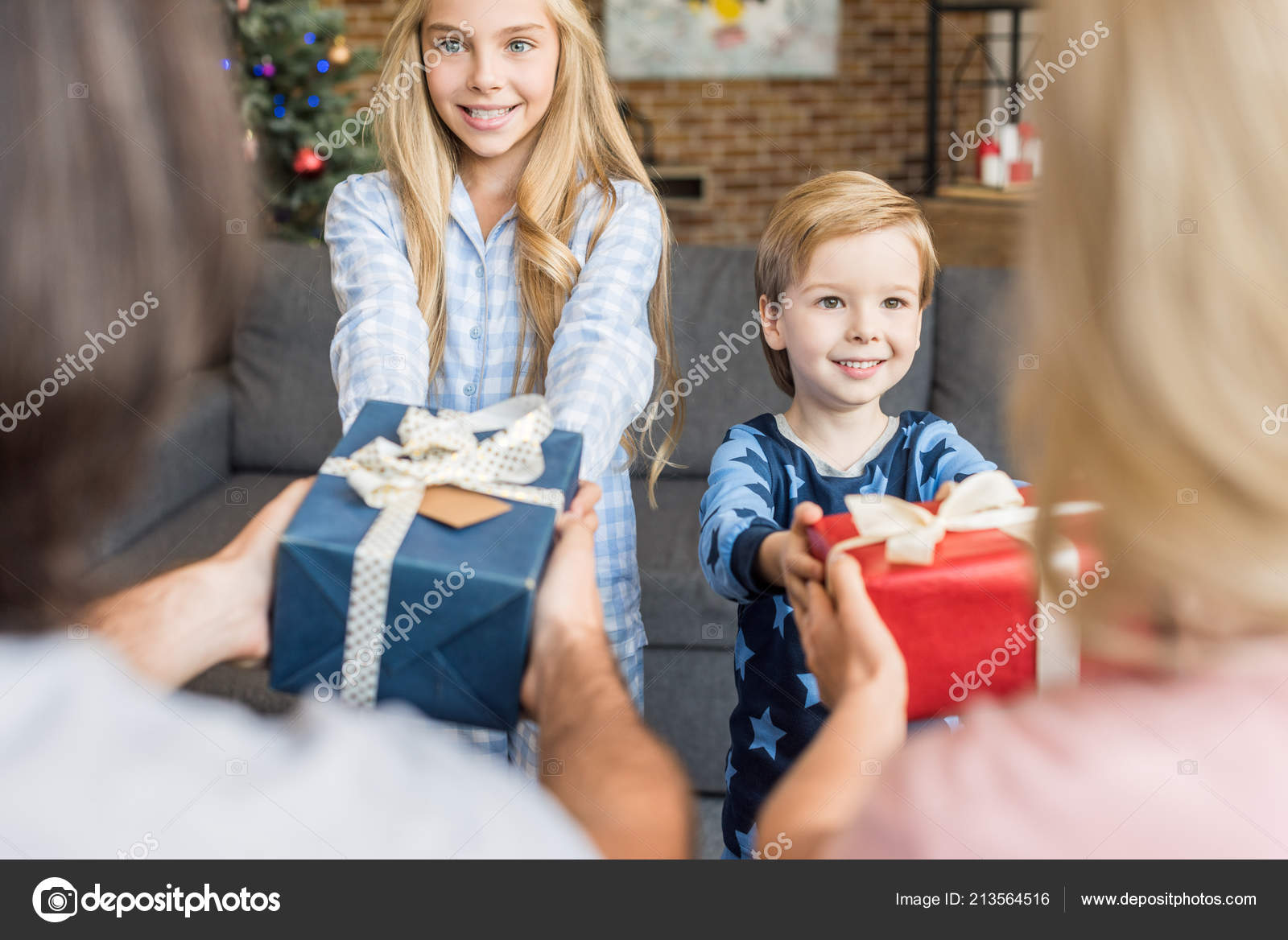 Cropped shot of parents presenting christmas gifts to happy kids in pajamas–  stock image e4a42b063