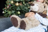cropped shot of kid hugging teddy bear and sitting on sofa at christmas time