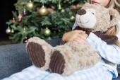Fotografie Oříznout záběr kid objímá medvídka a sedí na pohovce v době Vánoc