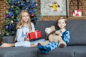 cute happy kids in pajamas holding teddy bear and christmas present while sitting in sofa and smiling at camera