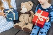 Fotografie oříznuté snímek šťastné sourozenci v pyžamu drží vánoční dárky
