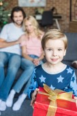 Fotografie adorable happy child in pajamas holding christmas present and smiling at camera while parents sitting behind