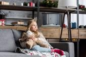 Fotografie schönen lächelnden Kind sitzt auf dem Sofa mit Teddybär und Wegsehen