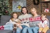 Fényképek boldog család két imádnivaló gyerekek, ül a kanapén, és mosolyogva kamera karácsonykor